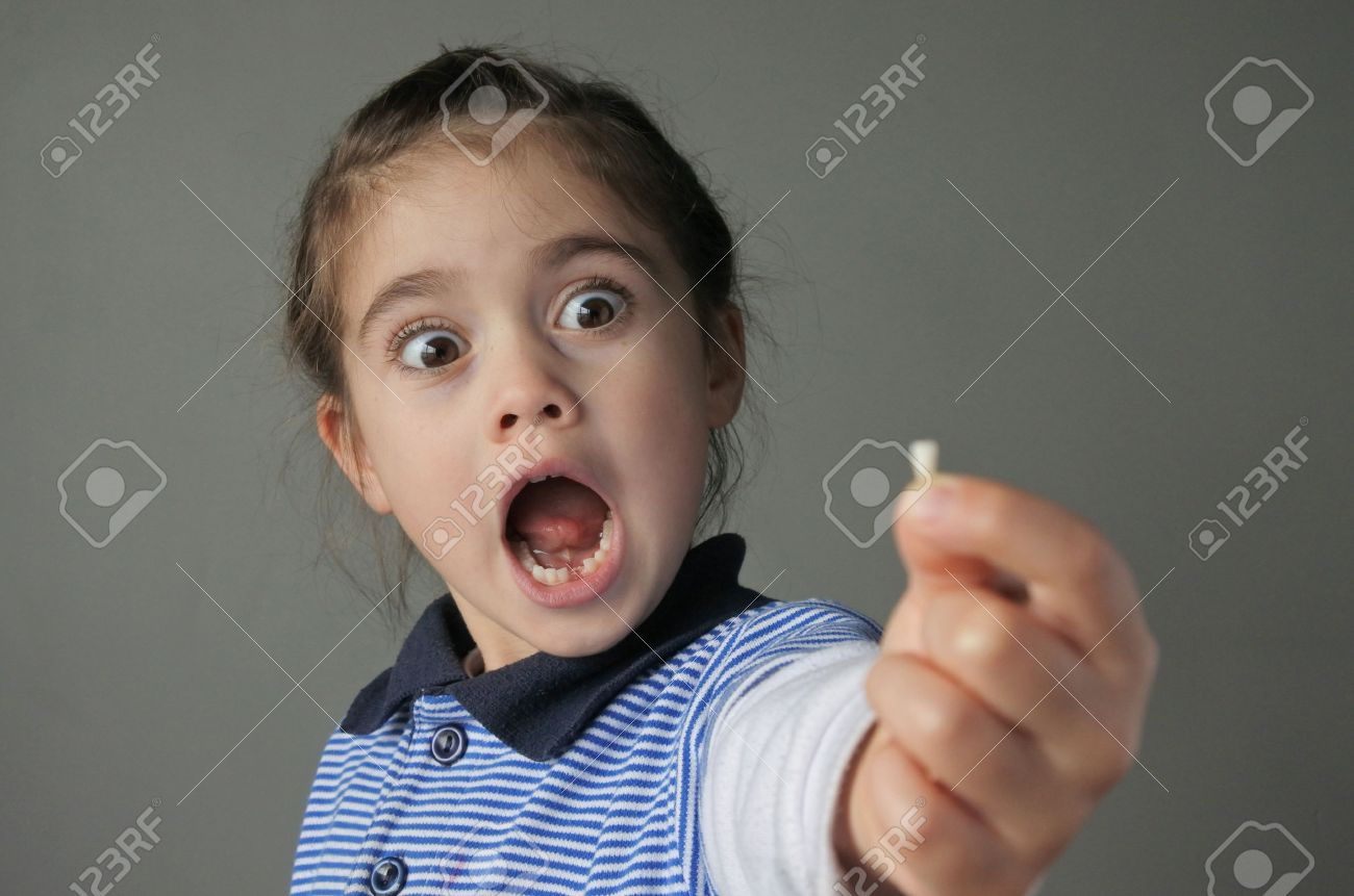 Young girl (age 6) surprise to find that she have lost her first bottom front milk teeth. Childhood healthcare concept. real people copy space - 62201464