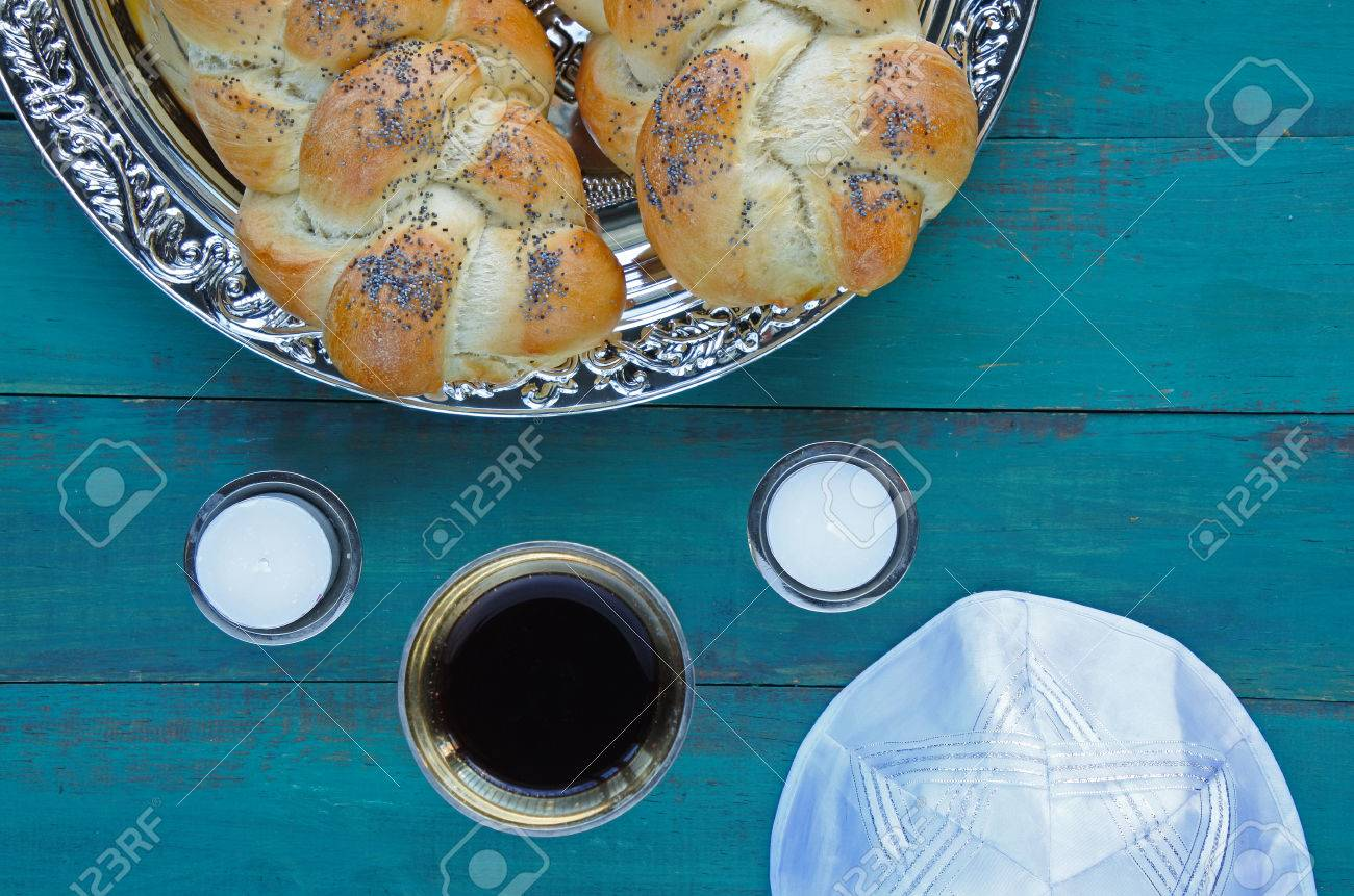 Flat lay view of Jewish Shabbat eve table meal with uncovered challah bread, Sabbath candles and Kiddush wine cup. copy space - 62201364