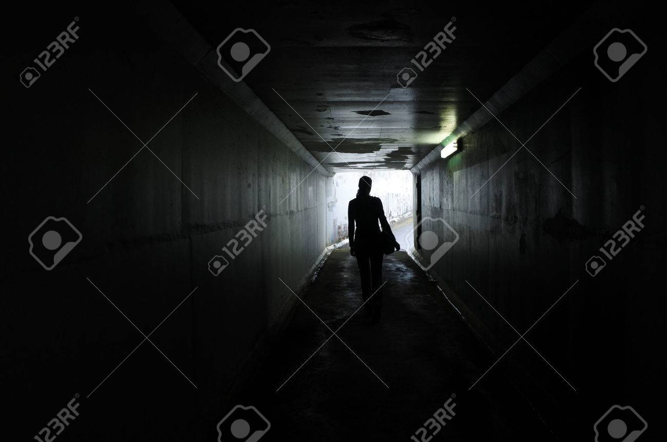 Silhouette of a young woman walks alone in a dark tunnel. Violence against women concept. Real people, copy space - 62168823