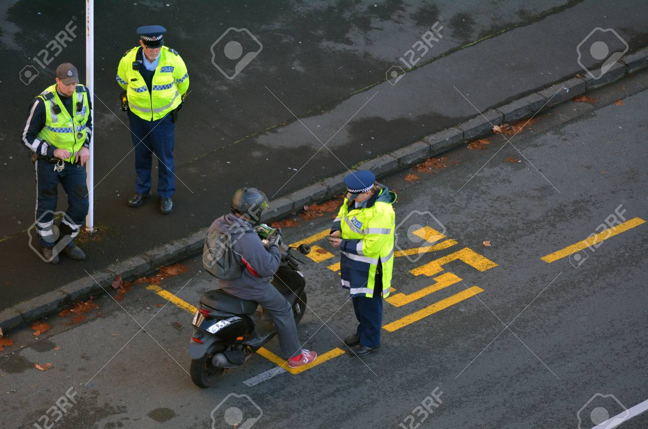 AUCKLAND, NEW ZEALAND - JUNE 08 2017: Traffic Police officer writing a traffic ticket to a scooter rider in Auckland city central, New Zealand. Traffic Police Monitor traffic to ensure motorists observe traffic regulations and exhibit safe driving procedu - 81822152