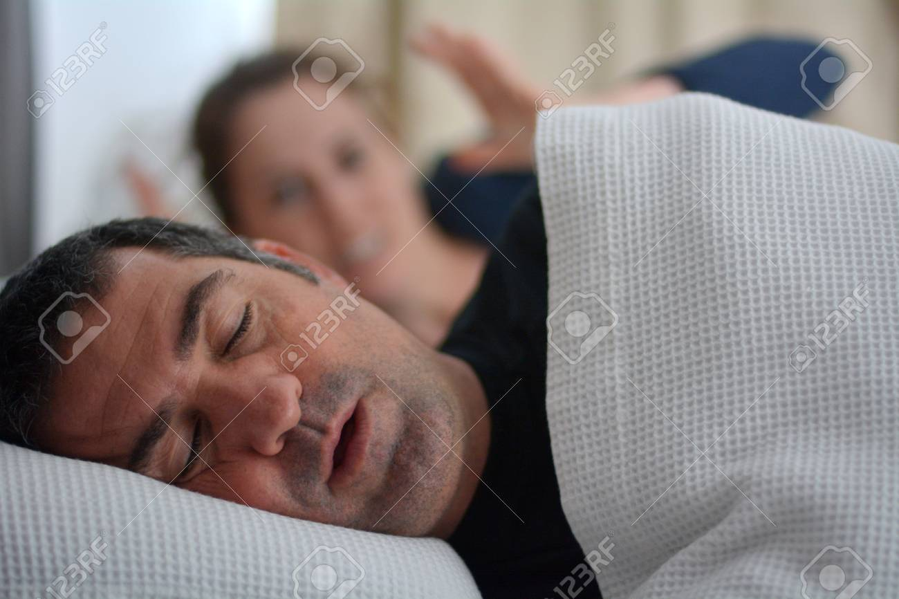 Woman (age 30) suffers from her male partner (age 40) snoring in bed. Noise concept. Real people. Copy space - 81761571