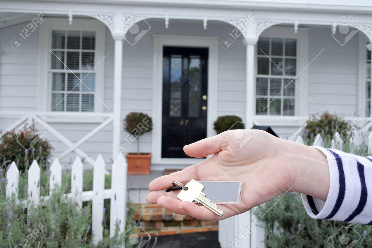 A womans hand holds a key against a front of a traditional villa house in Auckland, New Zealand. Buy, sale, real estate, insurance, mortgage, bank loans and housing market concept. - 86125653