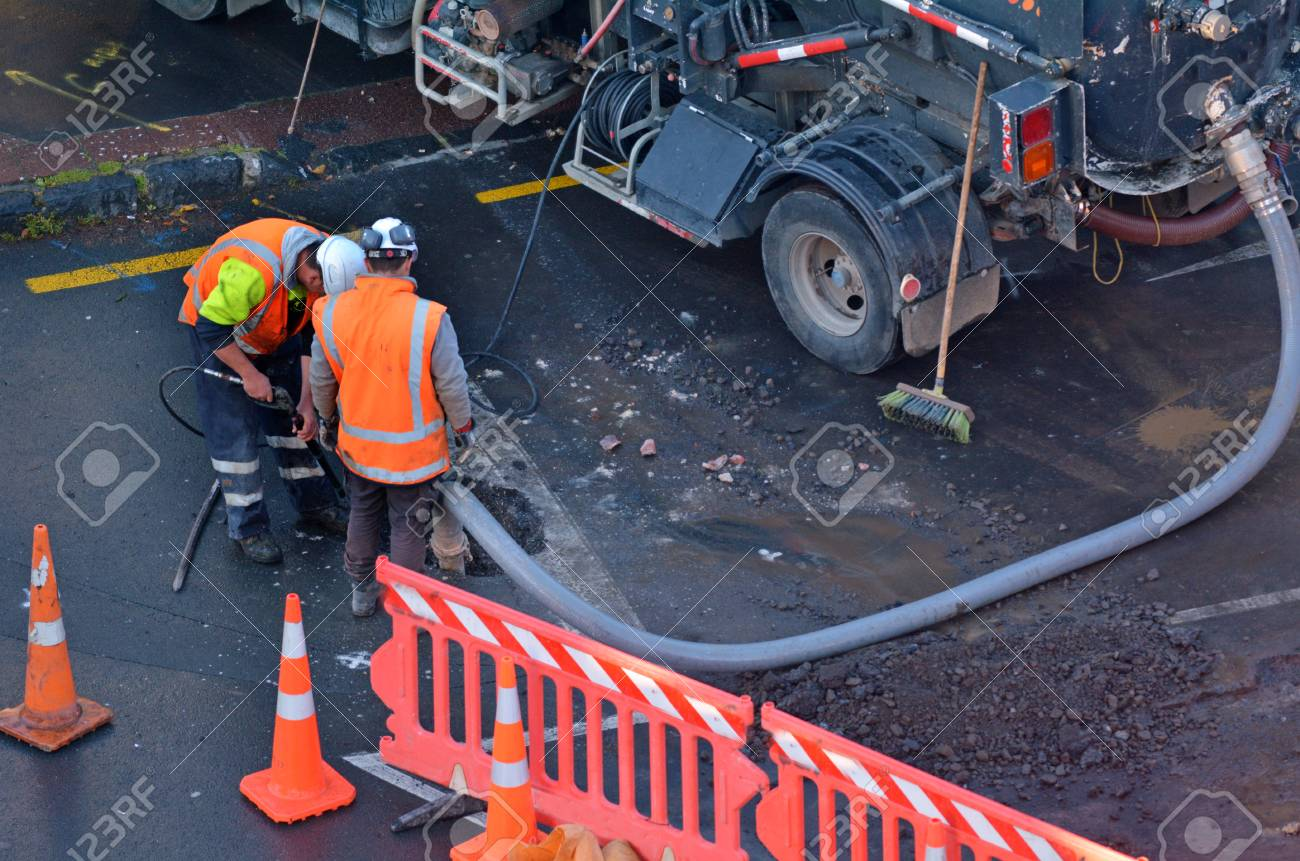 Unrecognizable road workers cleaning sewage in city street. - 87655263