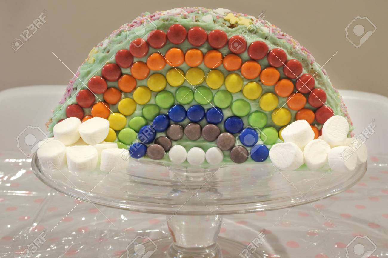 Rainbow Birthday Cake On Stand With Marshmallows And Colorful Lollie Food Background Texture