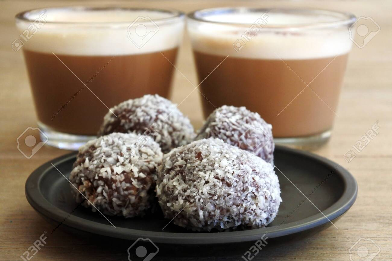 Sweet homemade Chocolate balls served with two cups of cappuccino drinks in a cafe. No people. Copy space - 142822922