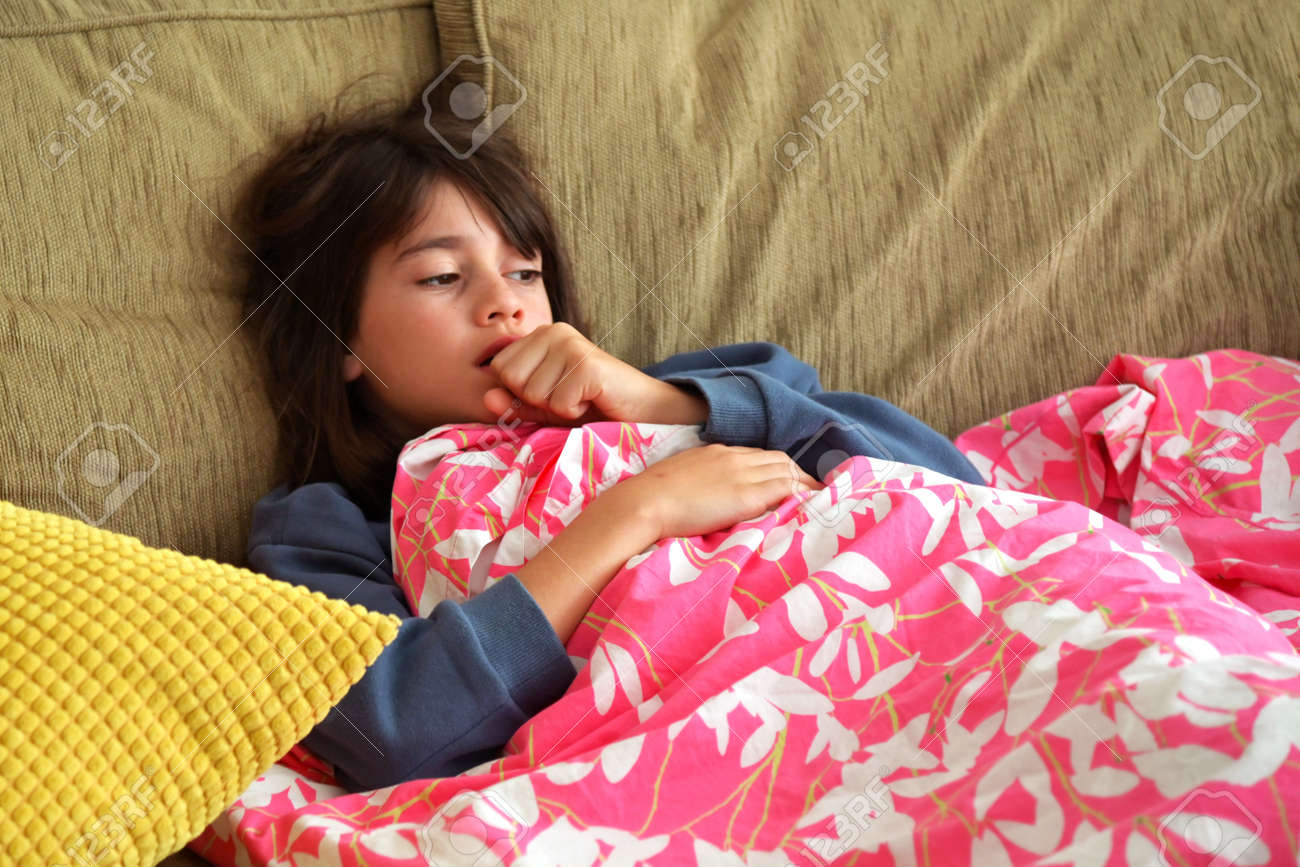 Young sick girl (female age 10-11) covered with blanket is coughing. - 168379474