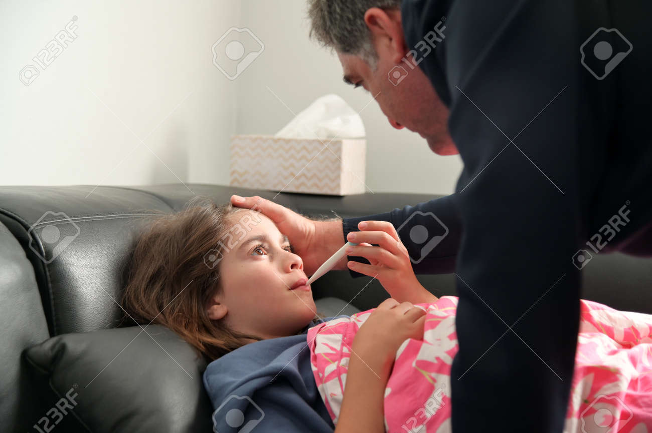 Caring father (male age 40-50) measuring body temperature to his young sick daughter (female age 10-11) covered in blanket lying on a sofa. - 168379479