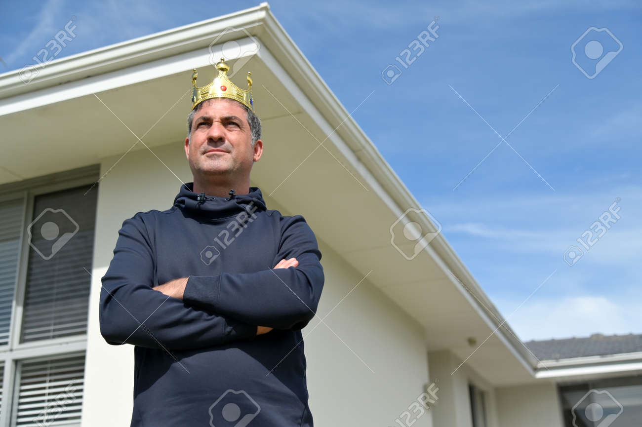 Confident mature adult man (male age 40-50) wearing king crown on his head with crossed arms standing outside his home, looking away from camera. - 168379492