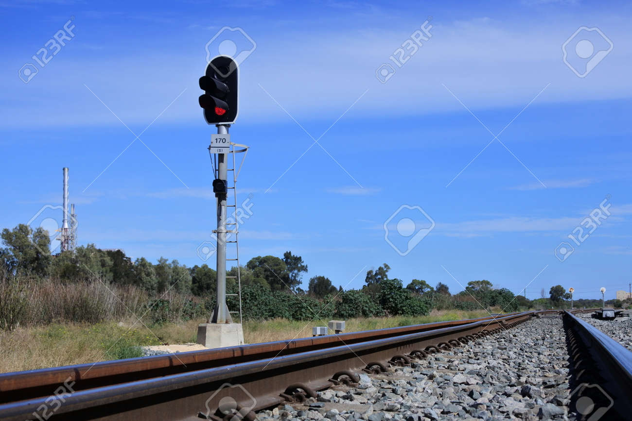 Railway signal on an empty rail way track near industrial site. No people. Copy space - 168379561