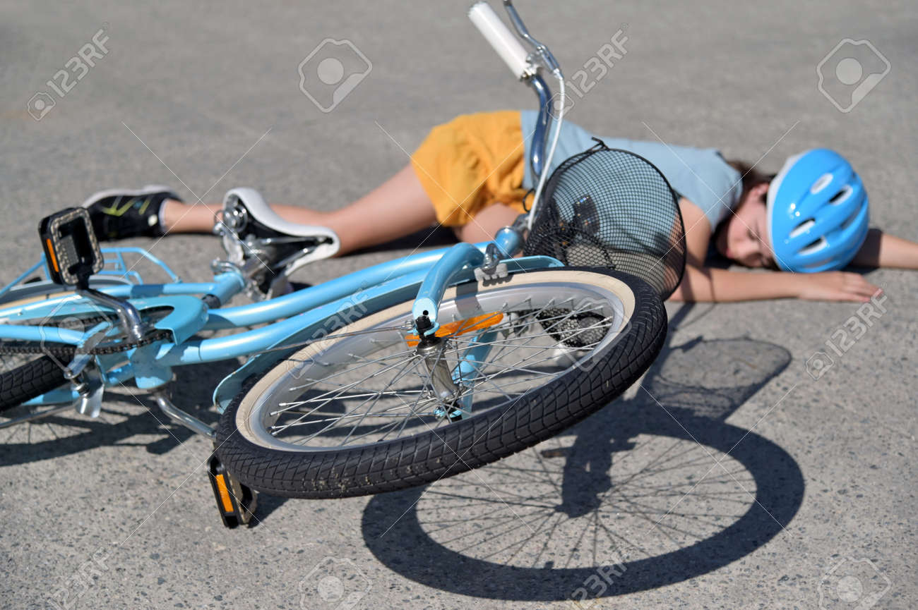 Young girl fallen of a bicycle laying down beside her bike unconscious on paved road. Real people. Copy space - 168379609