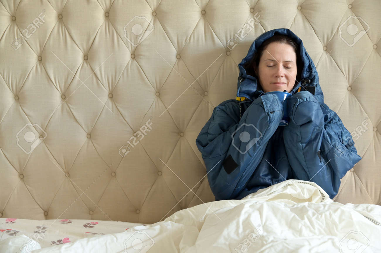 Happy adult woman wearing a very warm clothing and covered with a blanket, sitting on a double bed, having a hot drink in bedroom on a cold winter day. - 169904522