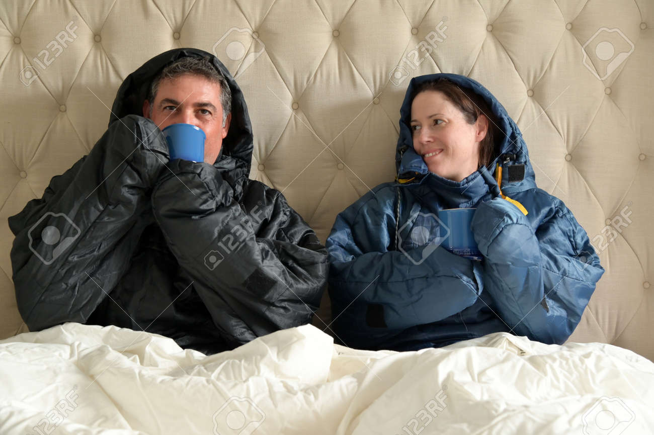 Happy couple sitting side by side wearing a very warm clothing and covered with a blanket, sitting on a double bed, having a hot drink in bedroom on a cold winter day. - 169904523
