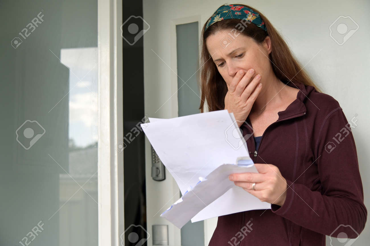 Shocked adult woman (female age 25-35) reading a letter outside a home front door. - 169904524