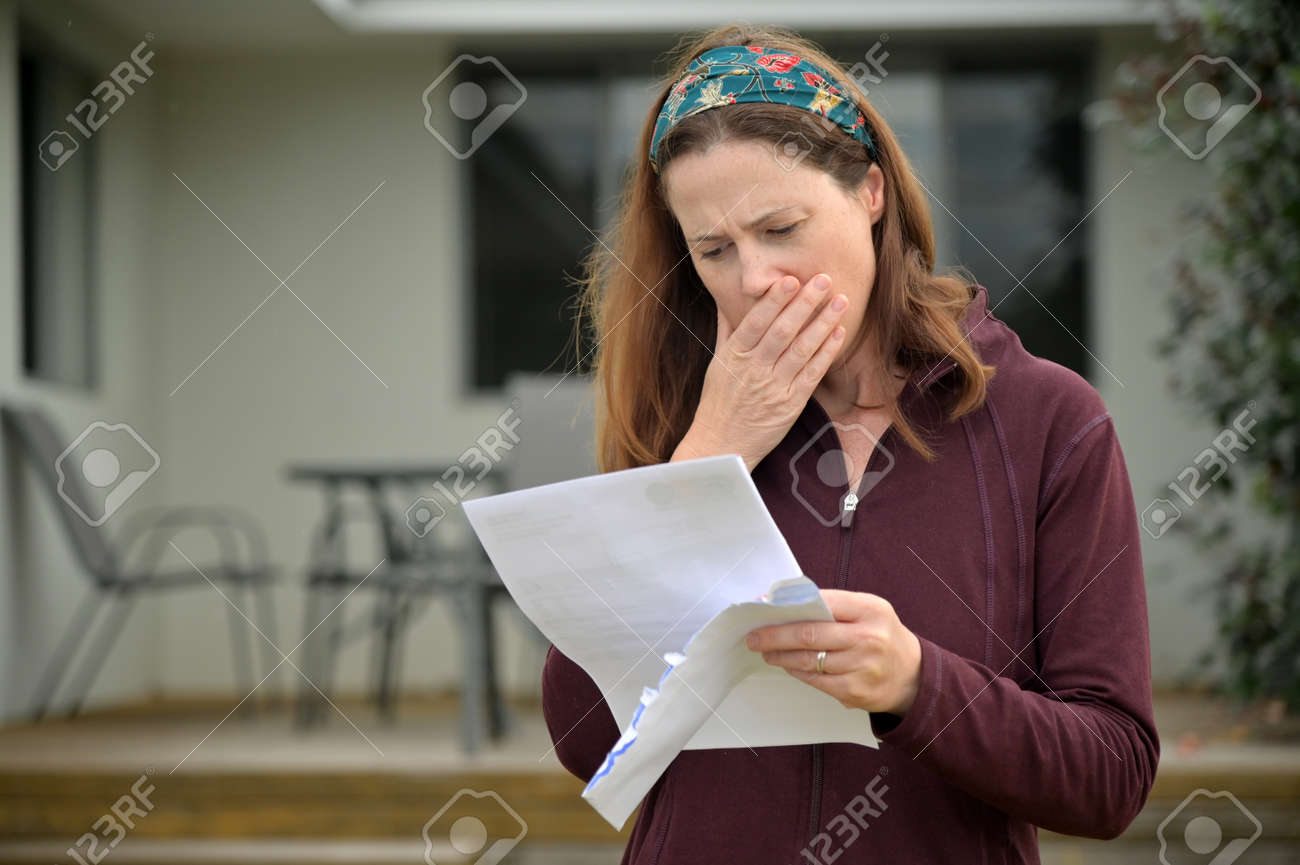 An upset adult woman (female age 25-35) reading a letter in home front yard. - 169904527