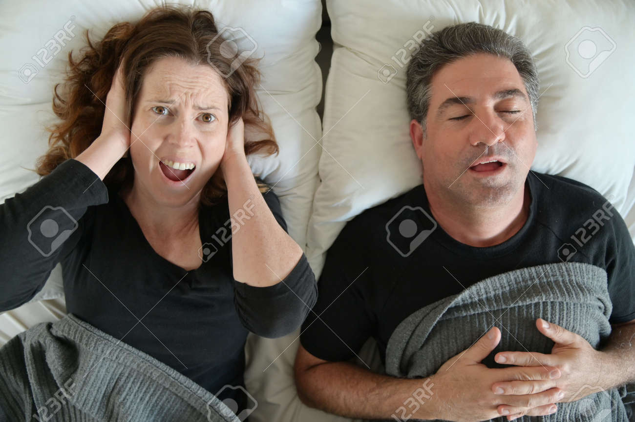 Upset mature adult man (male age 40-50) suffering from his partner an adult woman (female age 30-40) that snoring during sleep in bed. Couple lifestyle and people health care concept. - 169904562