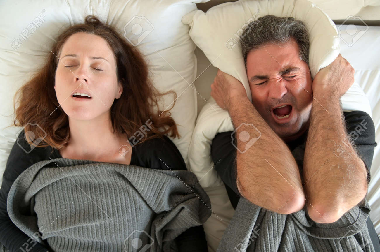Upset mature adult man (male age 40-50) suffering from his partner an adult woman (female age 30-40) that snoring during sleep in bed. Couple lifestyle and people health care concept. - 169904648