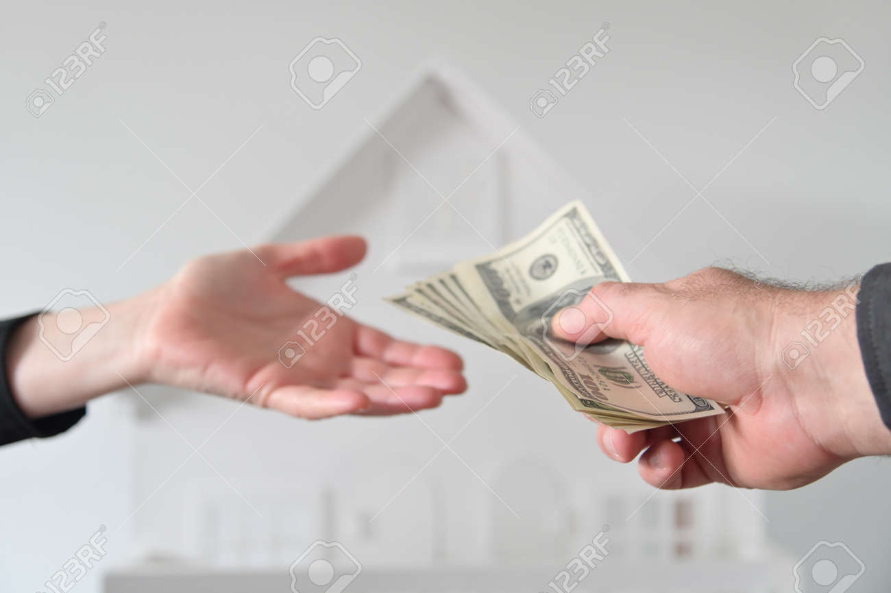 Two people (male and female) passing money against a white house. Mortgage, housing market, home loans and property, management concept. No people. Copy space - 169904659