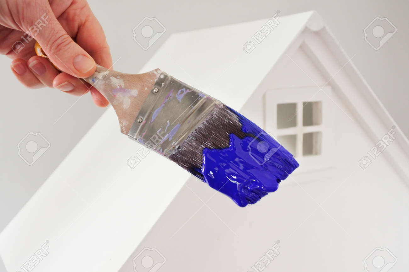 Person holding a paint brush with blue paint color against a white house. Renovation, home decoration and painting house concept. No people. Copy space - 169904660