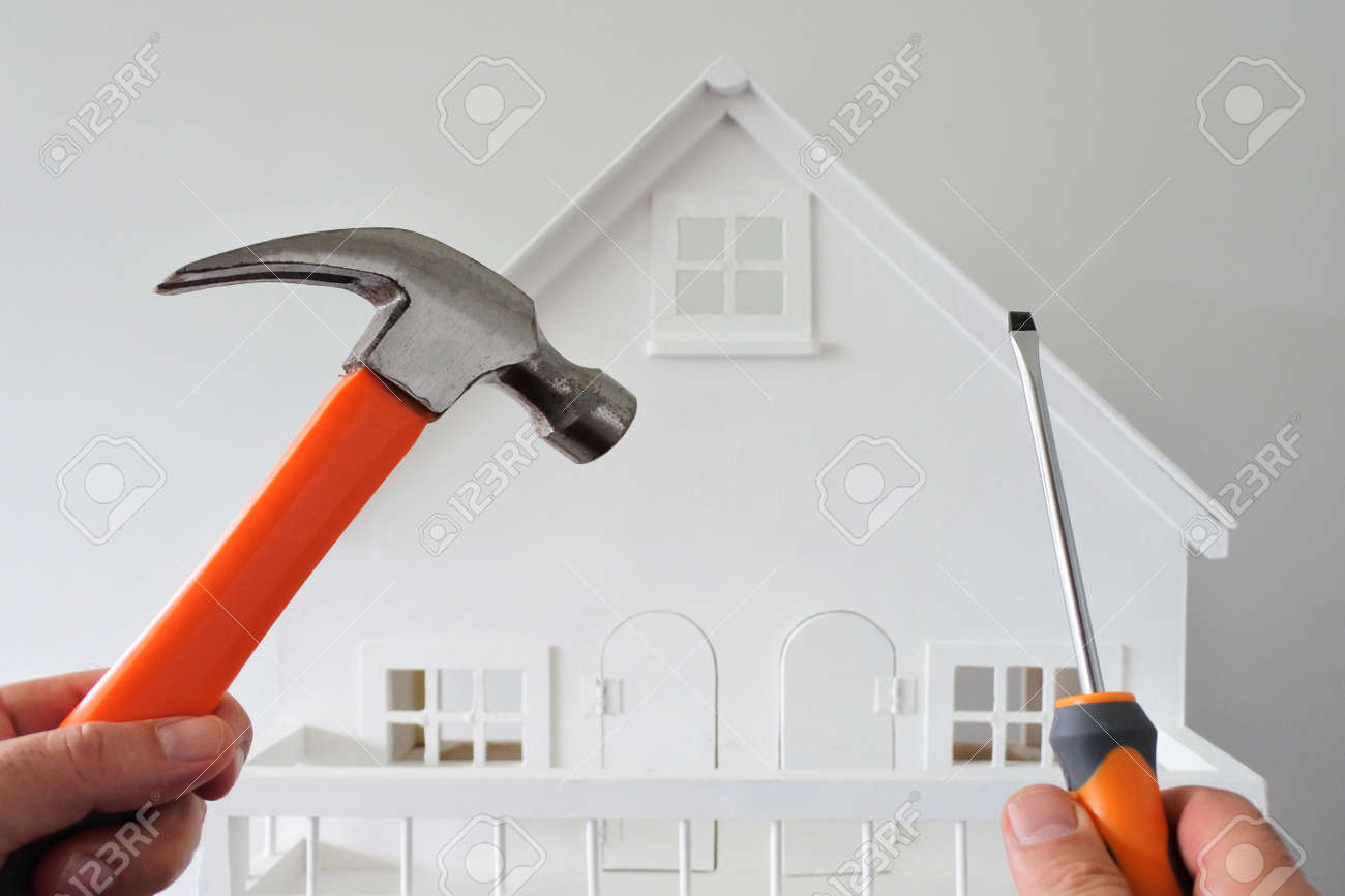 POV (point of view) of a person holding a hammer and screwdriver against a white house. Renovation, home decoration and painting house concept. No people. Copy space - 169904661