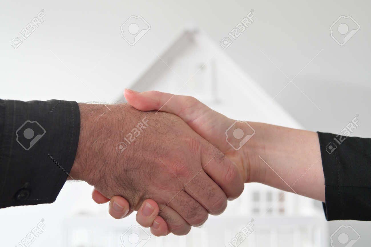 Two people (male and female) are shaking hands against a white house. Mortgage, housing market, home loans and property, management concept. No people. Copy space - 169904662
