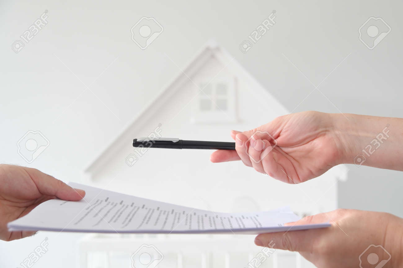 Two people (male and female) signing a contract against a white house. Mortgage, housing market, home loans and property, management concept. No people. Copy space - 169904665