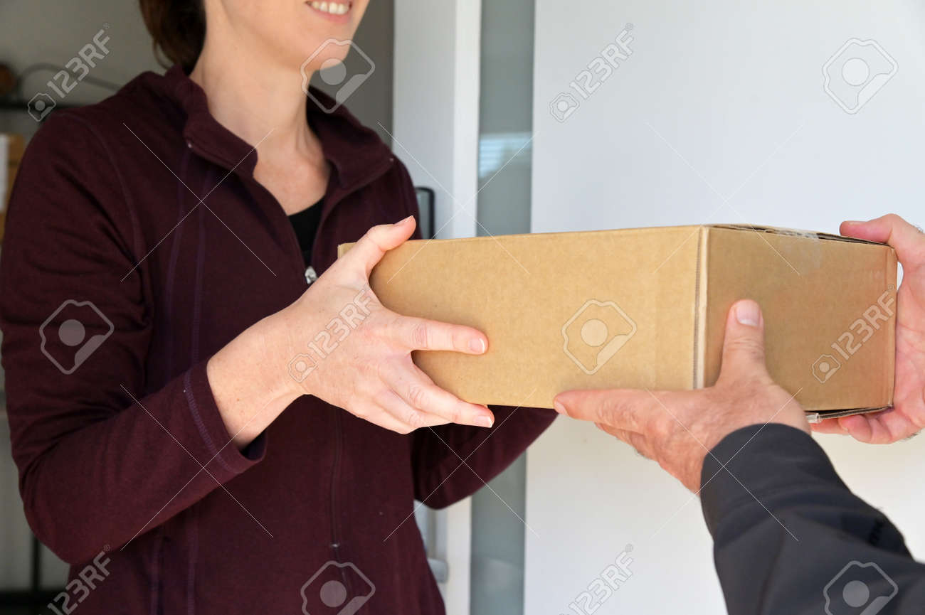 Woman receiving a package from a currier at home front door. - 169904669