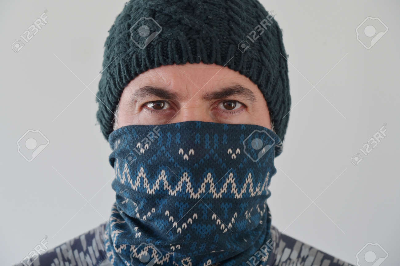 Middle Eastern Militant Man disguising his identity by wearing a beanie and balaclava face cover looking at camera. - 169904717