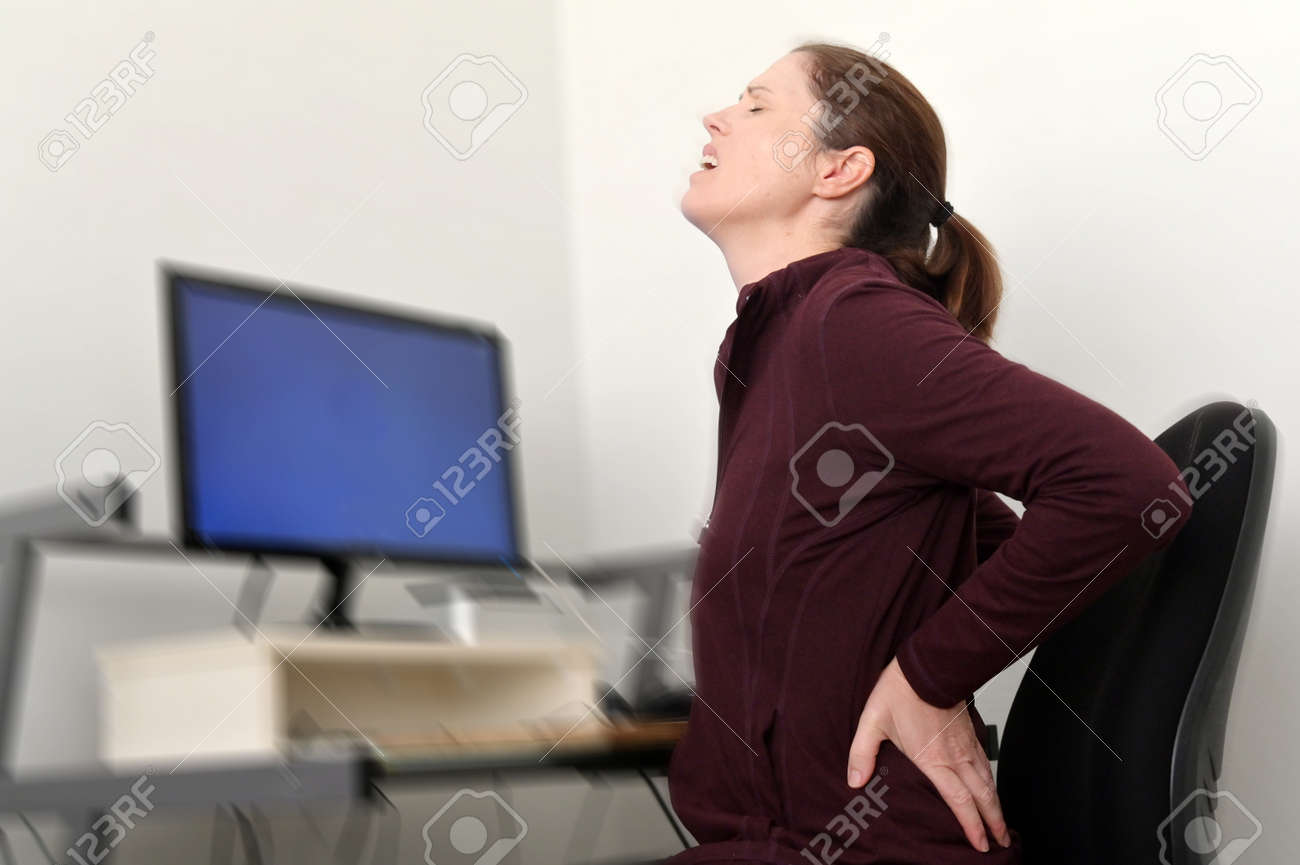 Woman working on a computer at a home office is suffering from lower back pain. - 169904719