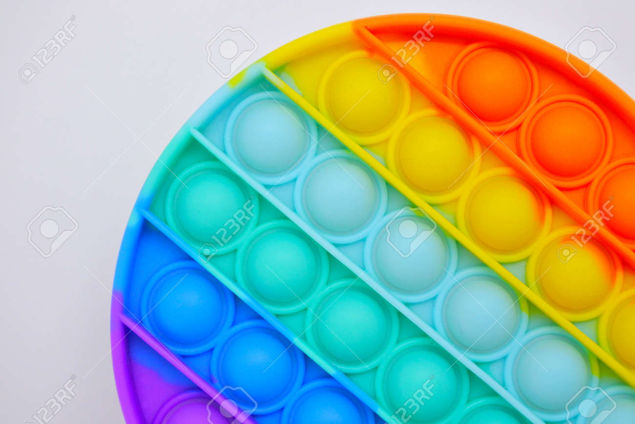 Close up of round Push pop it bubble fidget sensory toy in rainbow colors. - 169904766