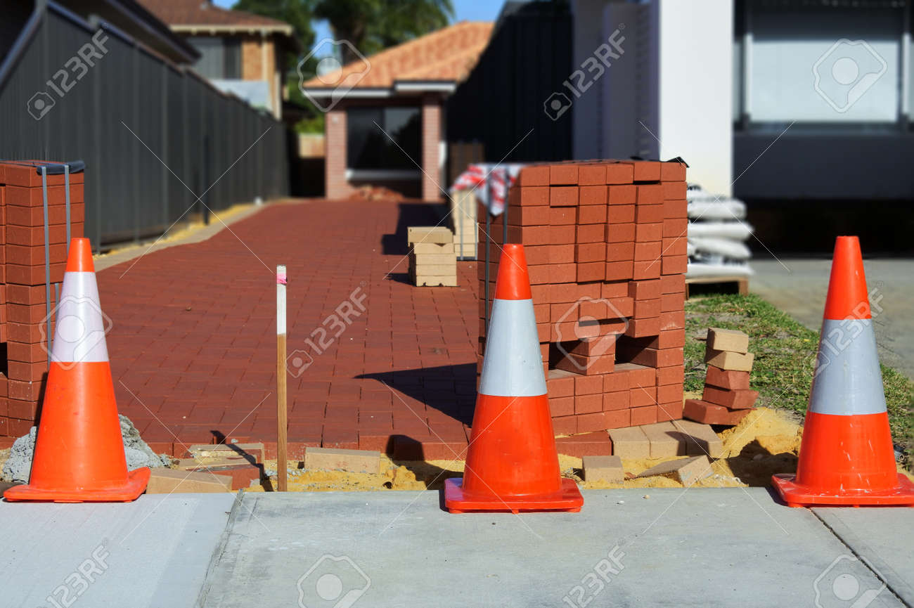 Line of a traffic safety warning cones in front of a new paved driveway with red bricks. . - 169904772