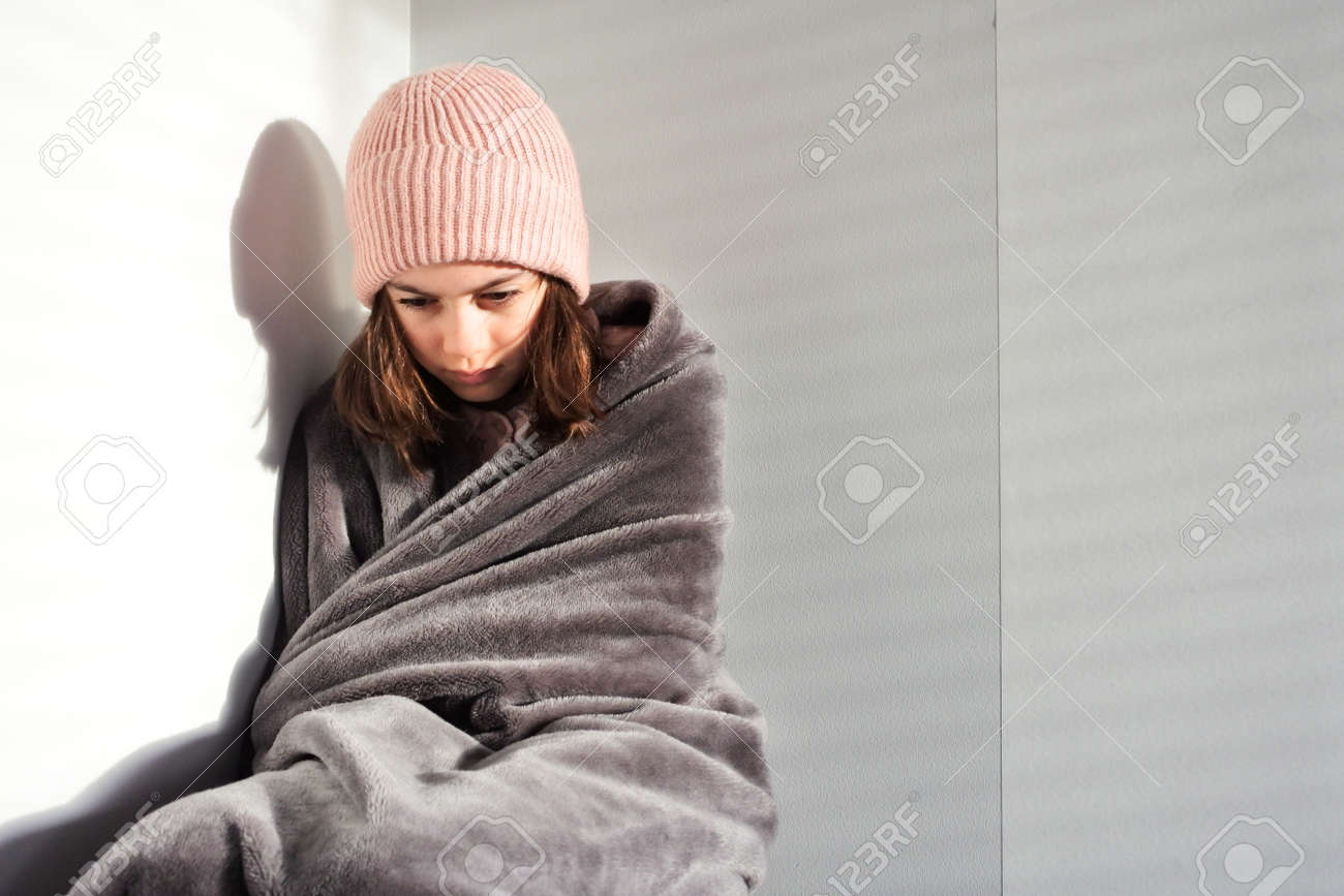 Sad young girl (female age 11-12) wearing a beanie sitting in the corner covered with warm blanket. Real people. Copy space - 169904773