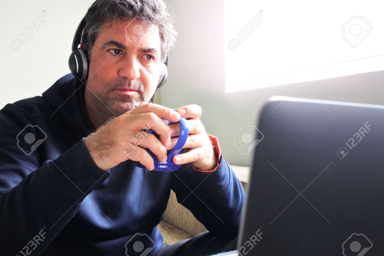 Worried unemployed mature adult man (male age 40-50) sitting on a couch watching bad news on a laptop at home office while having a morning hot drink.Uncertainty concept.Real people. Copy space - 169904775
