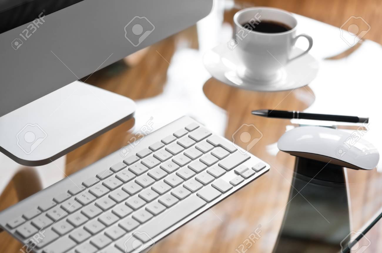 Bureau en verre avec un ordinateur moderne et tasse de café banque