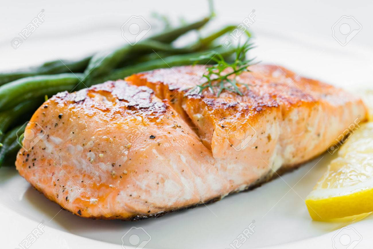 Close up of grilled salmon fillet with green beans and lemon on white plate - 43826375