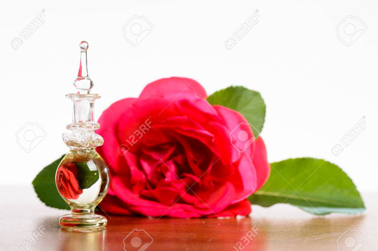 Small Bottle With Upside Down Image Of Rose That Is Lying Behind