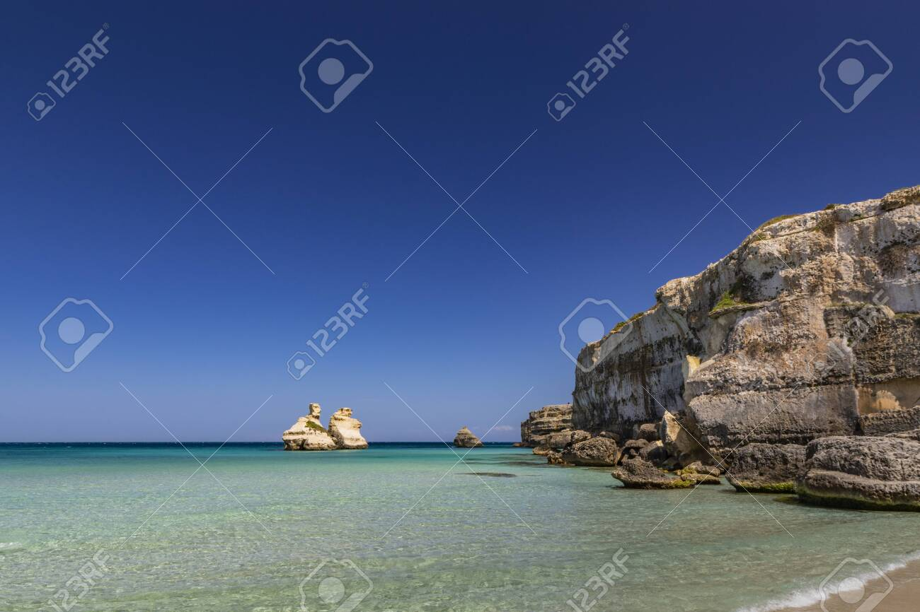 The bay of Torre dell'Orso, with its high cliffs, in Salento, Puglia, Italy. Turquoise sea and blue sky, sunny day in summer. A beach of fine white and pink sand. The stacks called the Two Sisters. - 148492947