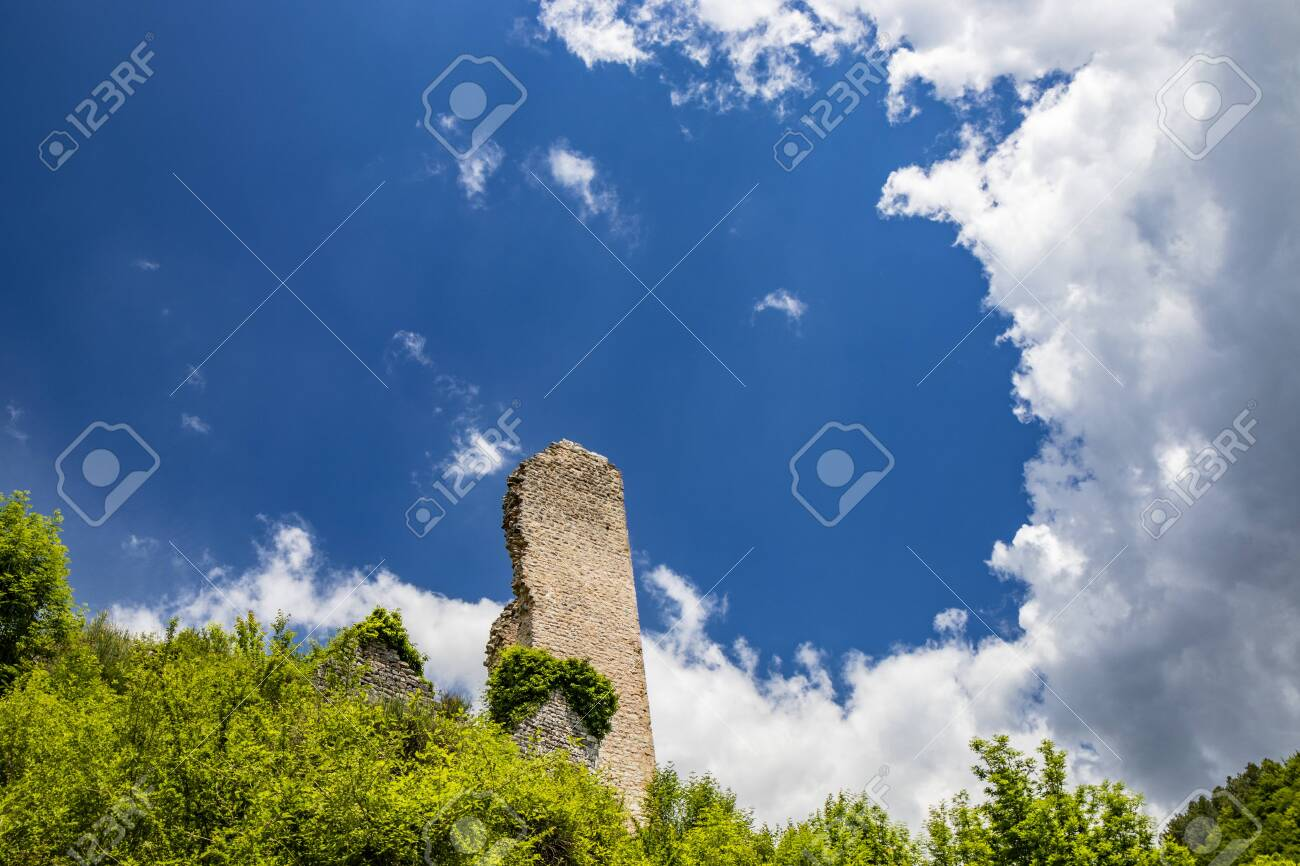 The ruin of the keep of the Trinci castle in Rasiglia. The remains of the tower, covered by vegetation, now collapsed and almost completely destroyed. The blue sky with clouds. Foligno, Umbria, Italy - 148869265