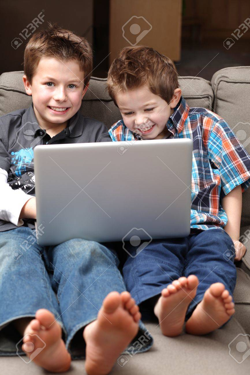 two cute boys on a couch surfing the internet stock photo picture