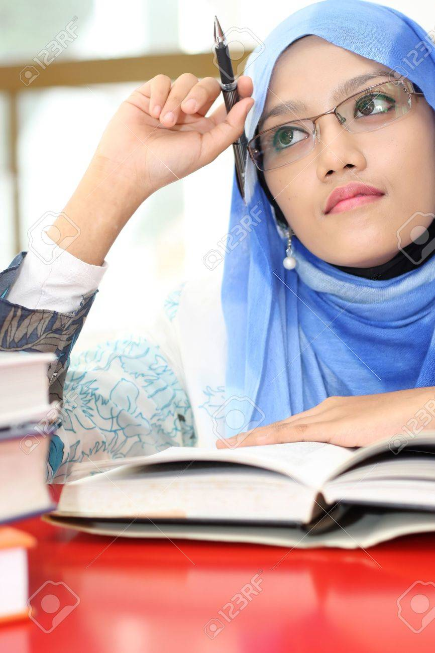 A young muslim girl reading a book while thinking Stock Photo - 10555406