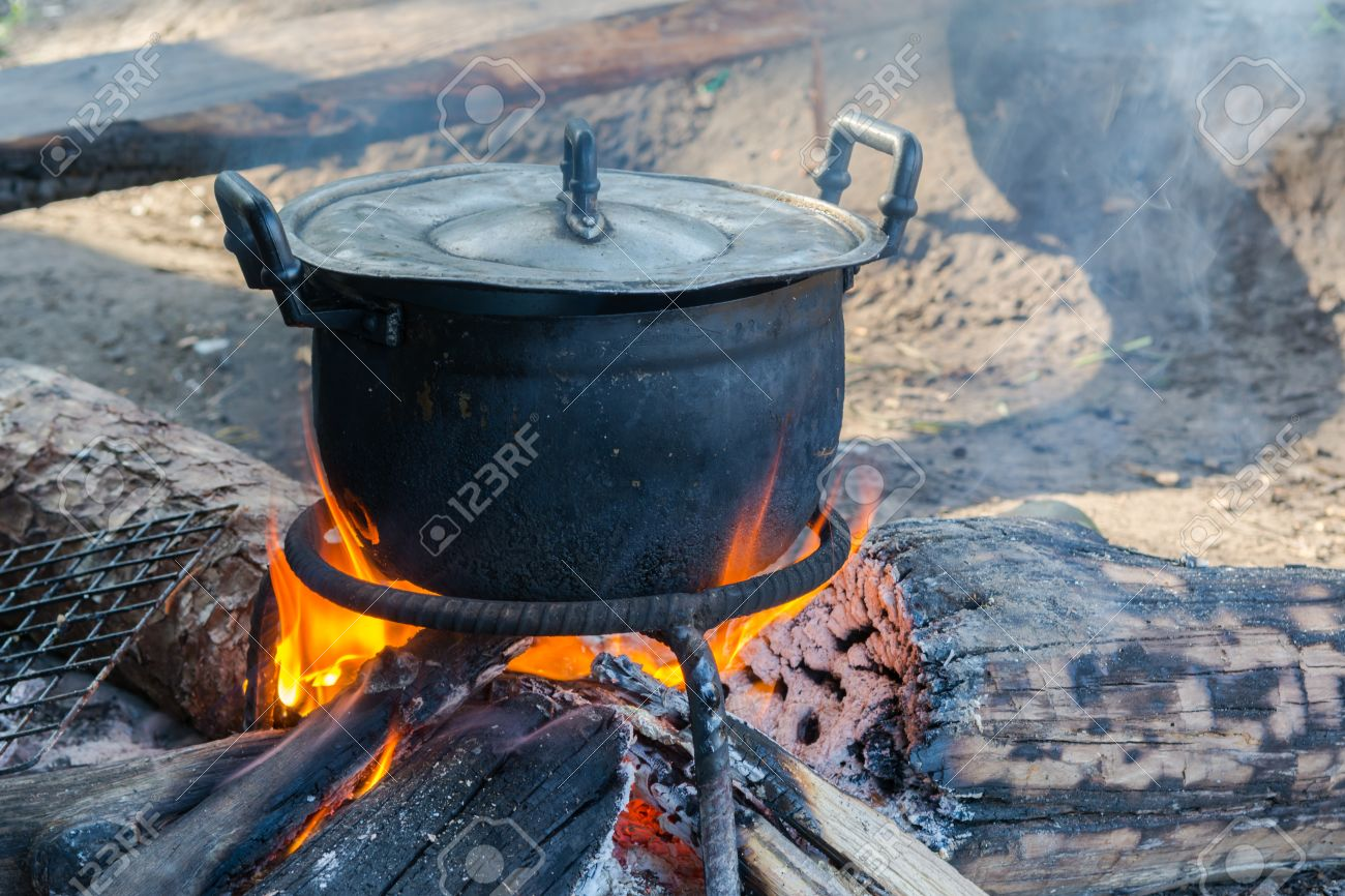 Stock Photo - black pot boiling water for cooking on the fired stove next  to firewood pile, Thailand Esan traditional culture ancient method - Black Pot Boiling Water For Cooking On The Fired Stove Next To