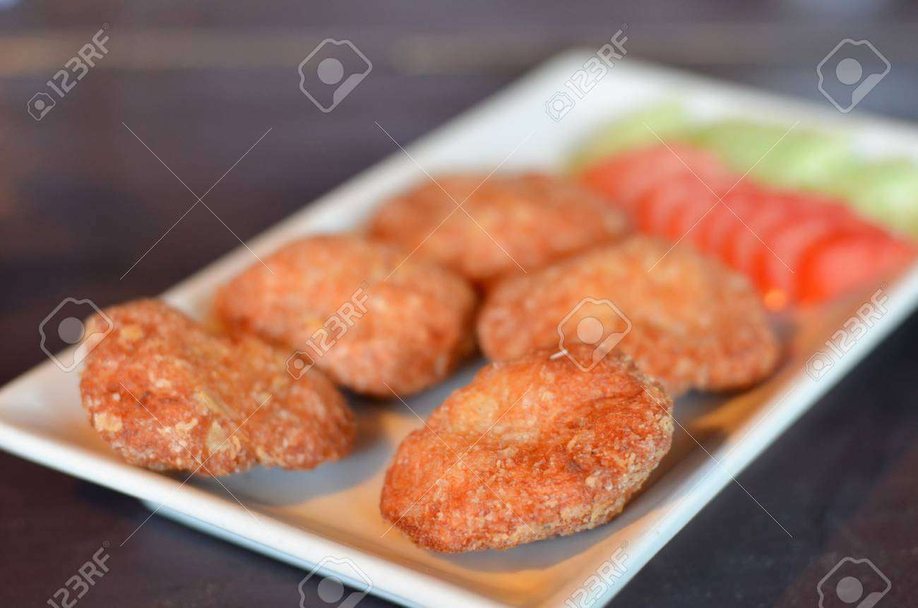 Spicy fried fish cake  Tod Mun Pla  served with cucumber and tomato Stock Photo - 13588960