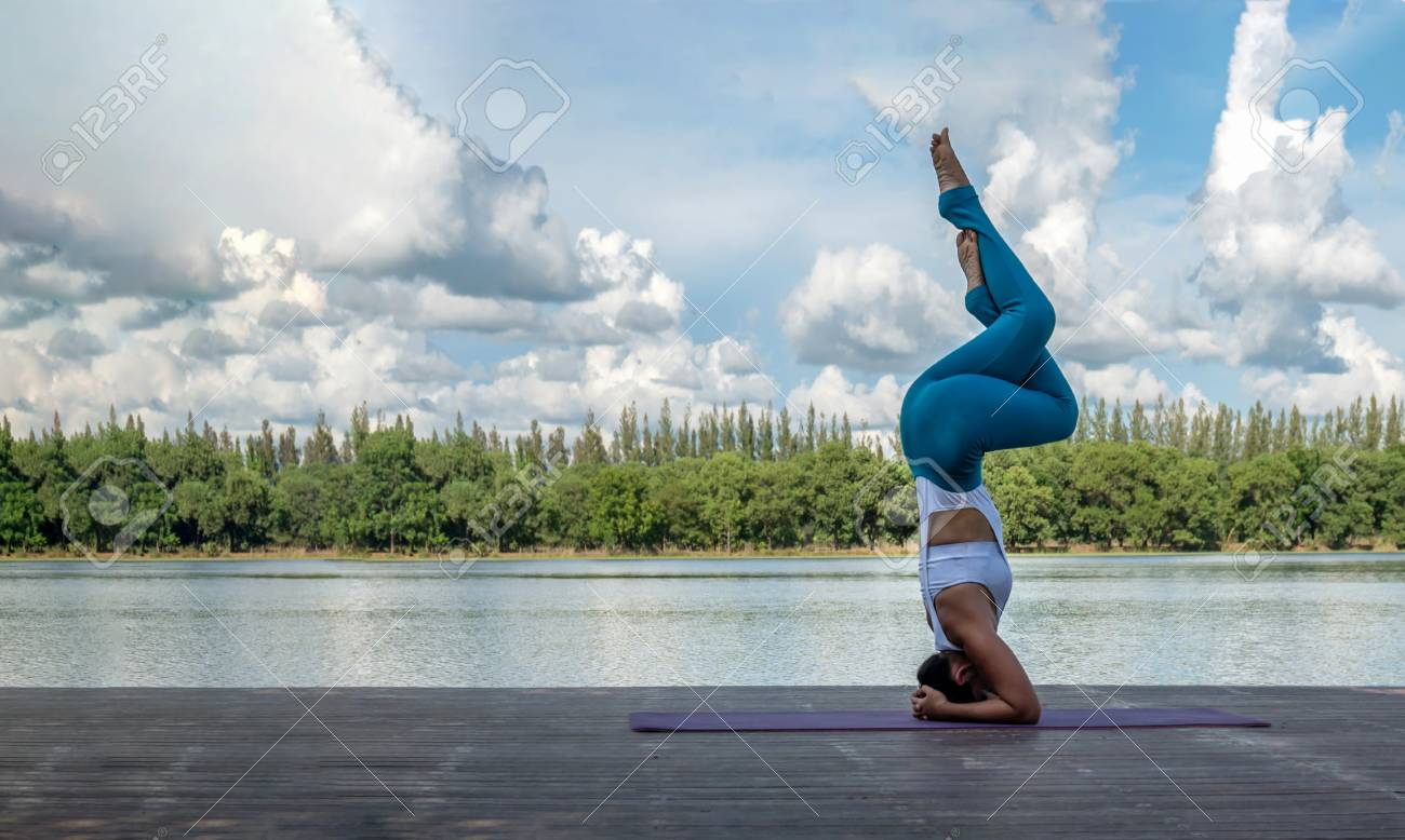 Asian woman practicing yoga pose , exercise outdoors with view..