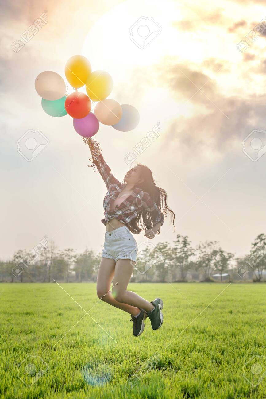 Portrait of a happy pretty woman with balloons in green field - 143130236