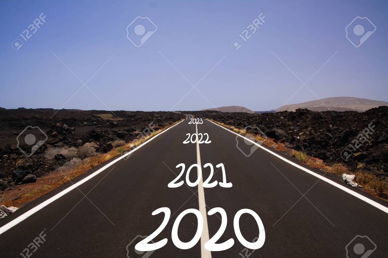 Long hard stony successful way concept: view on endless asphalt road through dry arid volcanic landscape with numbers of years 2020, 2021, 2022, 2023 - 140754604