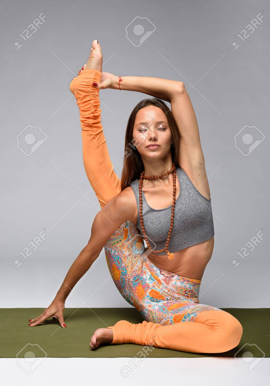 Yoga model practicing in sitting pose with one leg up