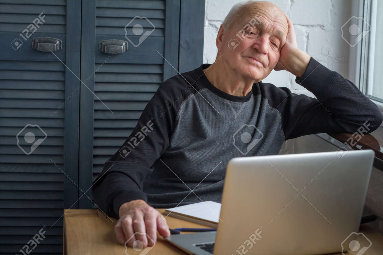 An elderly man is tired of looking at the screen of an open laptop, counting taxes, selective focus, free space for text. - 120655003