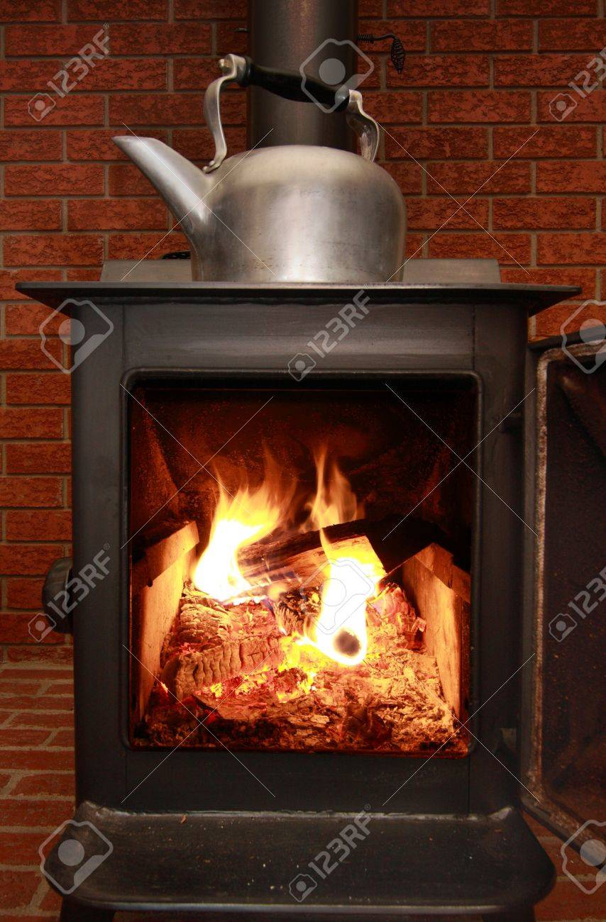 a view of a traditional wood burning stove and kettle stock photo