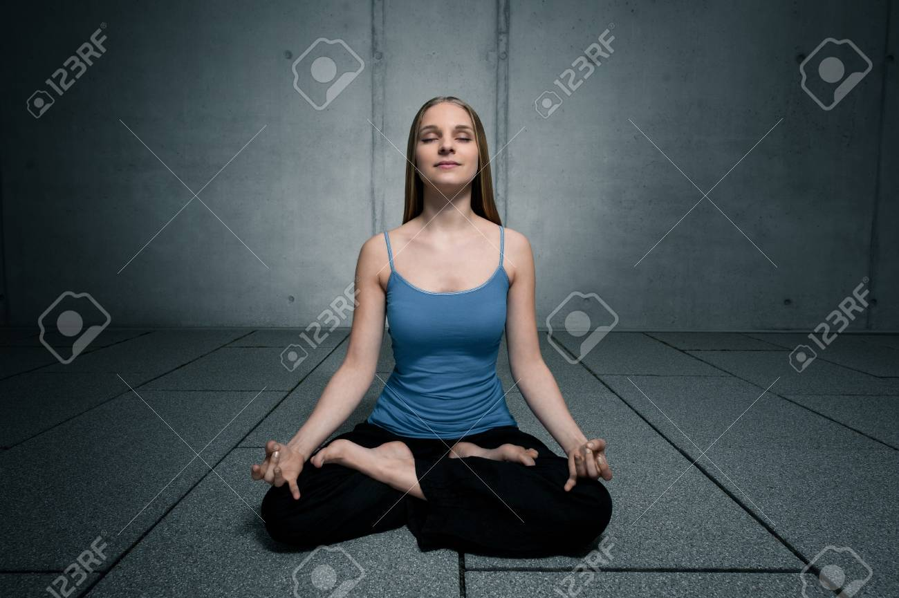 Young woman 20-25 sitting and meditating environment yoga meditation in a modern, cool, outdoor Stock Photo - 13265128