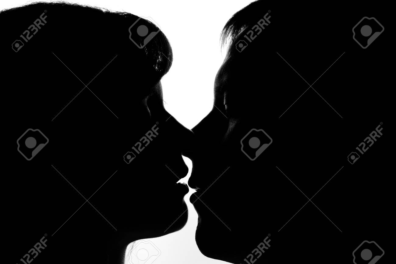 Black and white silhouettes of couples in love during a kiss stock photo 51422016