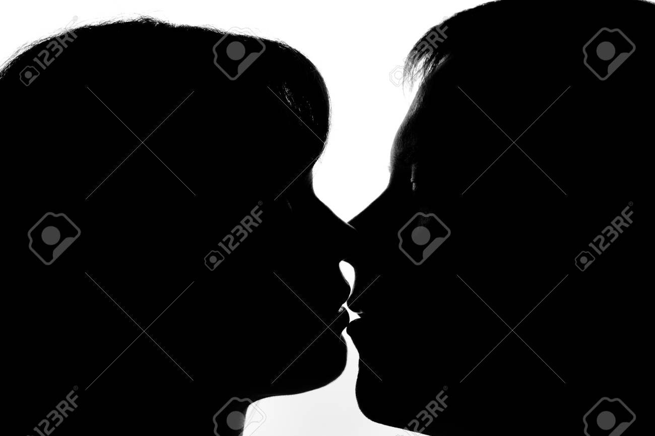Black and white silhouettes of couples in love during a kiss stock photo 51422017